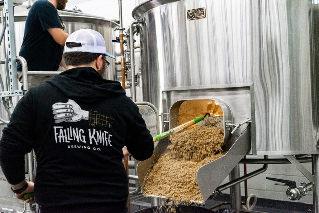 Falling Knife Brewing Co. brewer shoveling grains