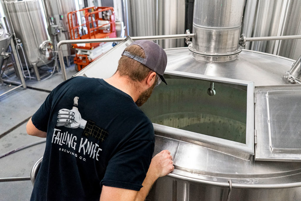 Falling Knife Brewing Co. brewer checking tank